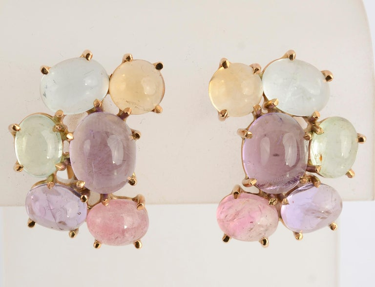 Crescent shaped cluster earrings with cabochon stones of amethyst; tourmaline and blue topaz. The colors are well combined to create a beautiful, soft palette.  Clip backs can be converted to posts. The earrings measure 1 inch in length and 3/4 inch