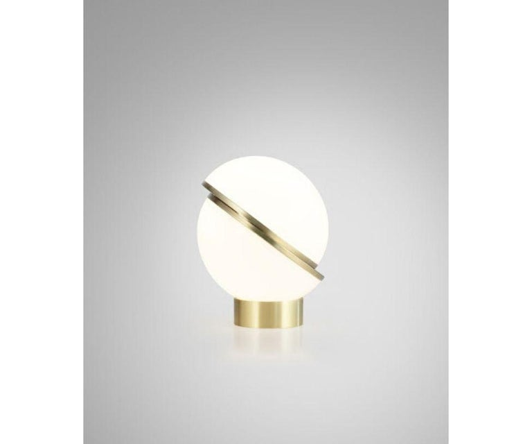 An illuminated sphere sliced in half to reveal a crescent-shaped brushed brass fascia, crescent seamlessly combines the solid and the opaque.  Technical specification Dimensions: Height 19.1 in x diameter 15 in Materials: Opaque acrylic, brushed