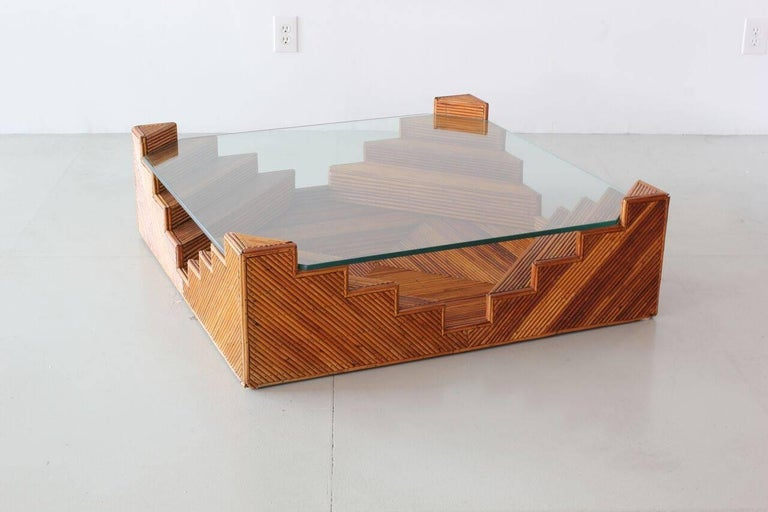 Incredibly unique rattan stacked coffee table with intricate design of rattan stacked in pyramid shaped corners with floating glass top.
