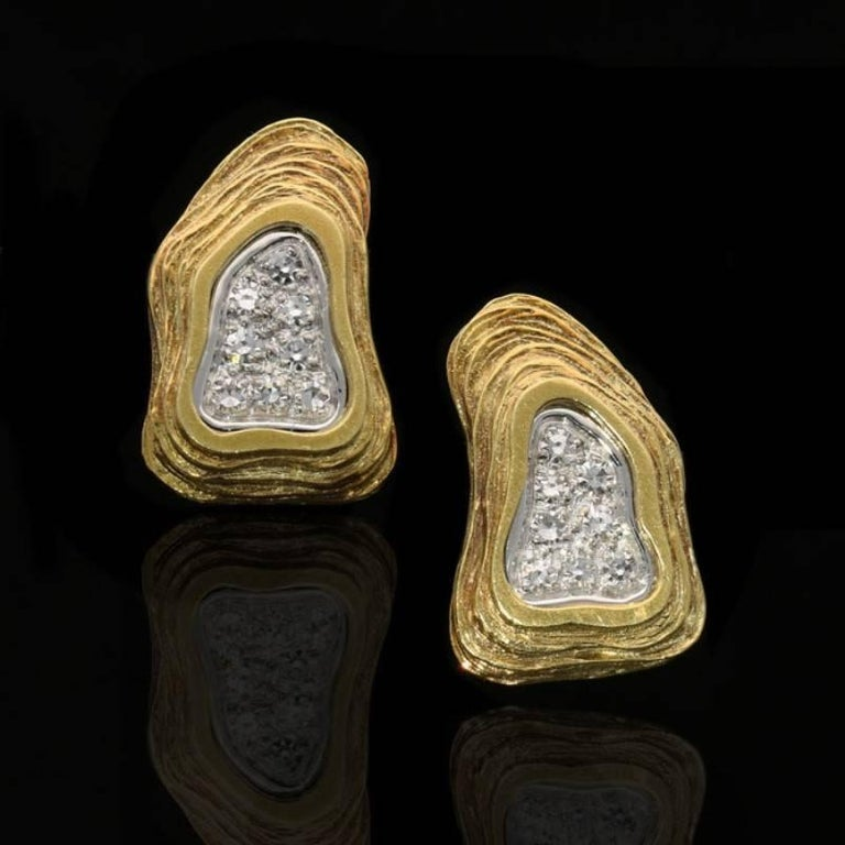 A striking pair of gold and diamond abstract earrings by Crinnan 1975, each designed as an irregular triangular disc of textured and stepped rows of 18 carat yellow gold wrapped around a central recessed free form area of single-cut diamonds pavé