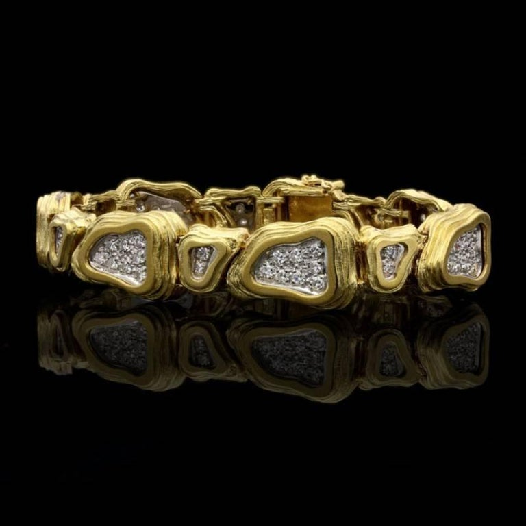 A striking gold and diamond abstract bracelet by Crinnan 1975, designed as a row of alternating larger and smaller links of similar irregular triangular shape set horizontally and vertically, each composed of textured and stepped rows of 18 carat