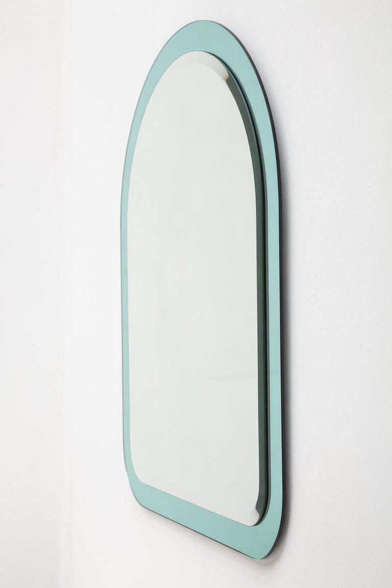 Vintage 1970s mirror designed by Cristal Art in a sleek arch shape features a clear glass mirror mounted on a frame of aqua blue mirrored glass. Mint condition.