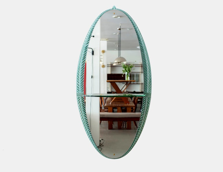 Gorgeous Cristal Art wall mirror, Italy, circa 1955. Ornate crystal cut glass detailing in oval shape with glass shelf and brass details Exquisite piece.