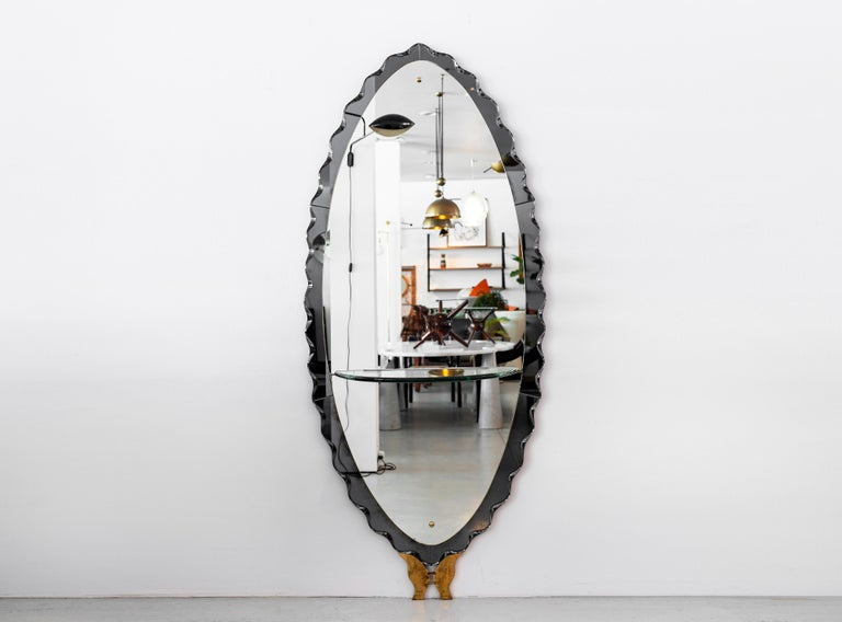 Stunning large full length mirror by Cristal Arte. Smokey grey glass border with a beautiful scalloped design. Thick cut glass shelf and brass butterfly detail at base. Unique and eye-catching piece!
