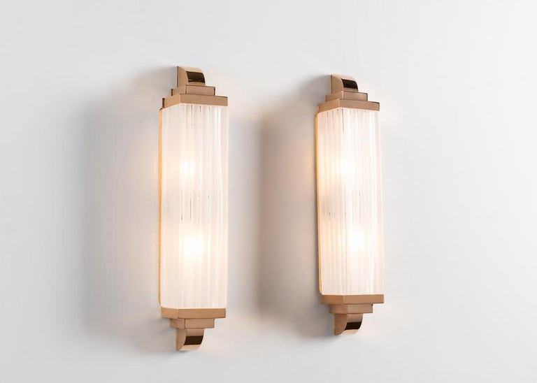 Composed of a long piece of meticulously hand carved crystal and two pieces of well articulated bronze, this elegant sconce carries forth the Deco tradition in which the first of the Benito family's extraordinary craftsmen learned and plied their