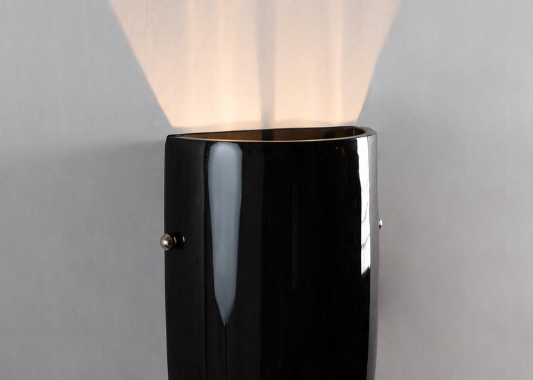 This elegant sconce's unique presence can be attributed to Benito's unique use of obsidian, a mineral stone 2-3 million years old, which diffuses light at its vertical seams, shooting the rest of it skyward, and reflecting that from without.