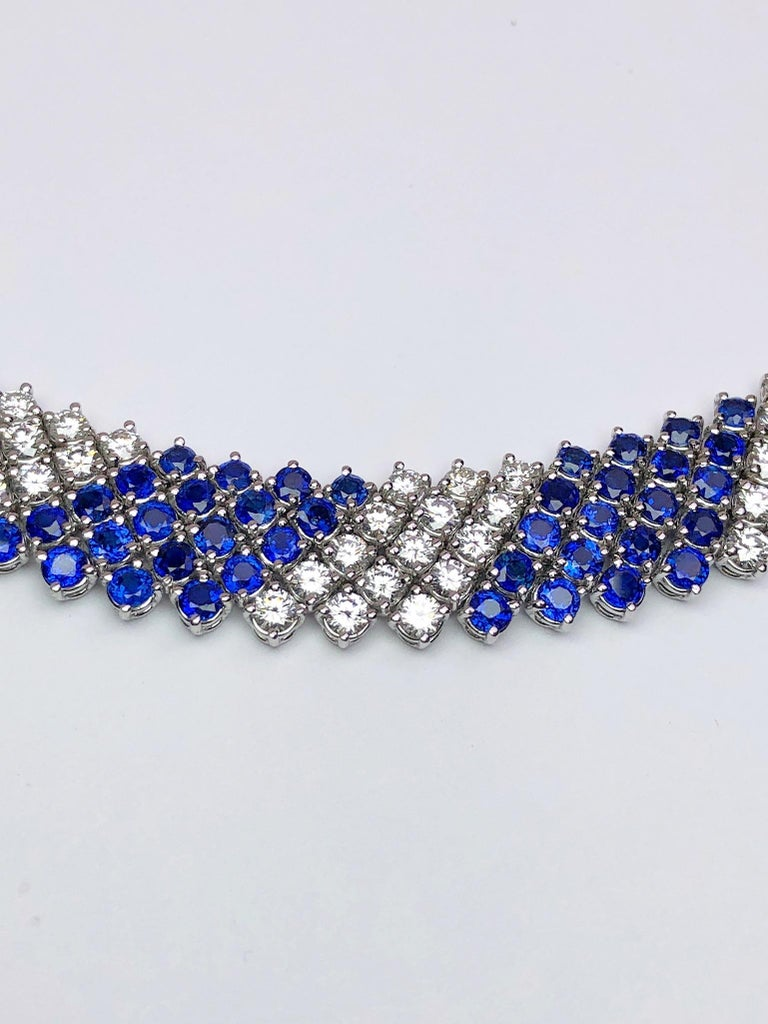 This lovely designed collar necklace by Crivelli is entirely set with 5 rows of round brilliant Diamonds and Blue Sapphires. The alternating stones and the flexibility of the setting will lay beautifully around the neck. The necklace measures 16