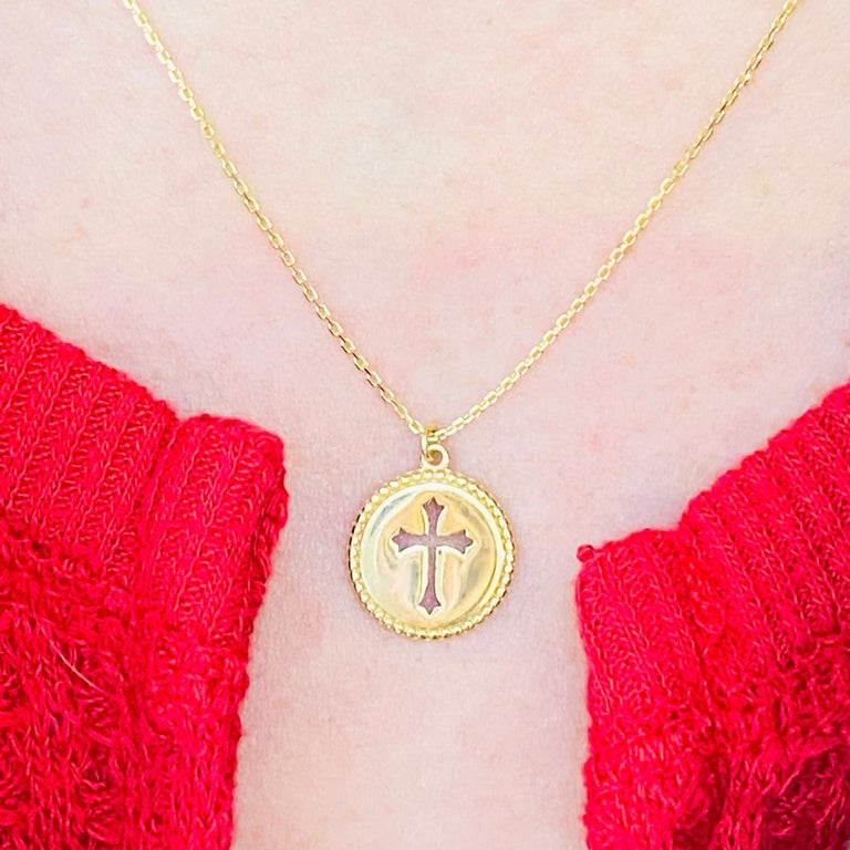 This gorgeous, intricate cross disk pendant is a stunning and striking design. The cross pendant is made in solid 14 karat yellow gold. The disk design has handmade millgrain texture. This pendant is on an 18 inch cable chain that compliments the