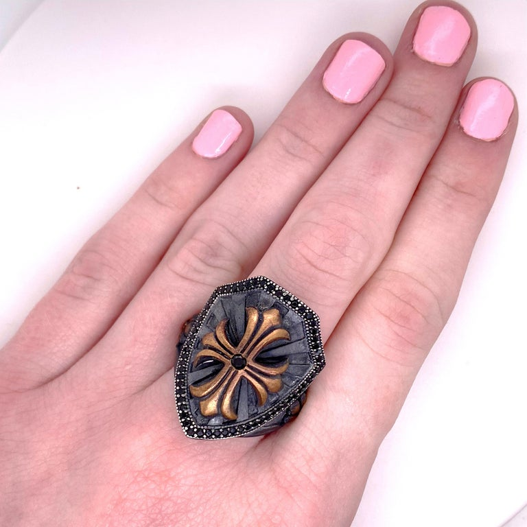 This cross shield ring brings the wearer great power! The handmade sterling ring is solid and very significant. It has a gorgeous raised cross in the center with a ruby in the center and the outline of the ring is encrusted with black onyx. There is