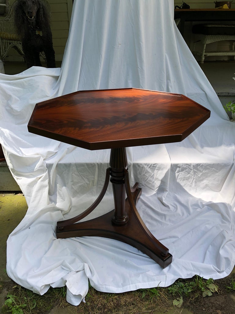 Sheraton style octagonal table in beautiful crotch mahogany on a tripod pedestal base. Base decorated with black painted stringing.