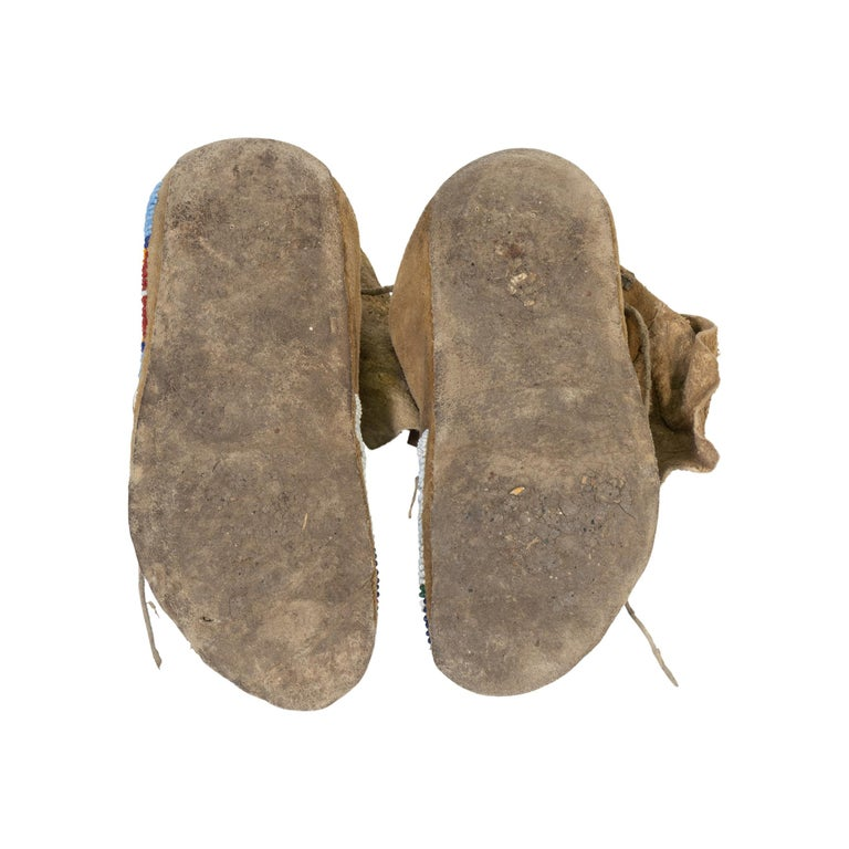 Crow youth moccasins with parfleche soles, red faceted beads and brain tanned doe skin. Traded with the crow in the 1930s by the owner of a mercantile in Xabier, Montana.  Period: circa 1900 Origin: Crow, Montana Size: 8