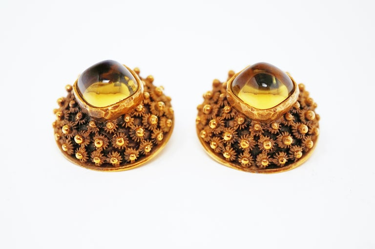 These stylish Brutalist-style clip-on statement earrings by Trifari (circa 1960) are a must-have for costume jewelry collectors.  Truly a statement piece, these earrings are domed and gilded with an antiqued finish. Two Amber-colored glass cabochons