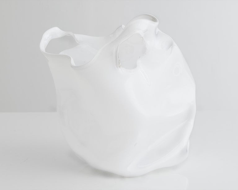 Unique crumpled sculptural vessel in white hand blown glass. Designed and made by Jeff Zimmerman, USA, 2014.  Limited number available. Please note that each item may differ slightly in color and shape.