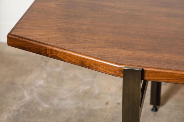 The Cruz dining table features a geometric wood top made of American walnut or white oak and modern plated steel legs. Shown here in light walnut and antiqued brass.   Available to order in various finishes with a 10-12 week lead time.