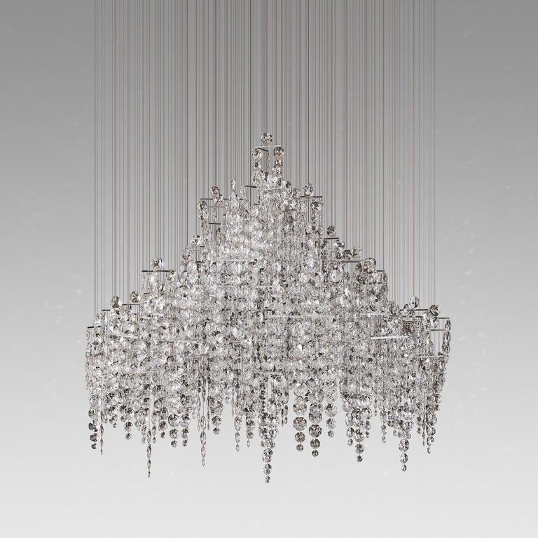 A signature chandelier by renowned illumination artist Eva Menz, a stunning, free floating re-interpretation of a Classic candelabra.  Each strand is furnished with a carefully polished trapeze suspending several strands of hand-strung high grade