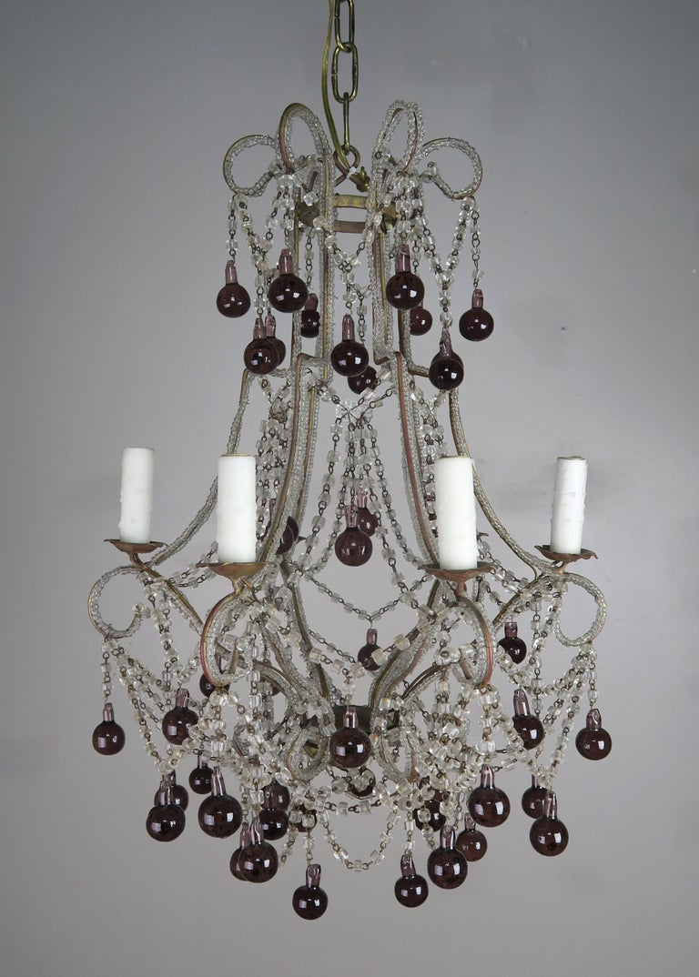 Crystal beaded frame macaroni chandelier adorned with aubergine colored drops throughout. The fixture is newly rewired with drip wax candle covers. Includes chain and canopy.