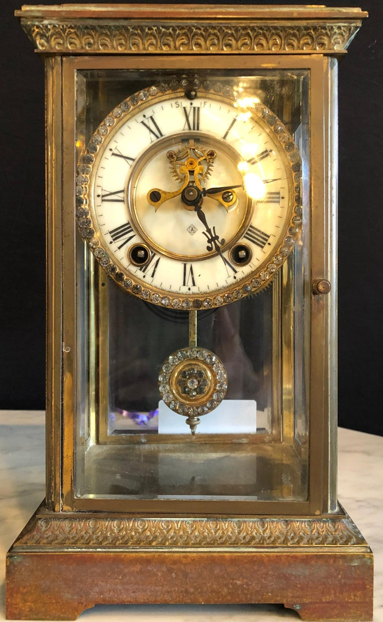 Crystal face and pendulum clock made by Ansonia Clock of New York. Bronze case in all beveled glass surround.