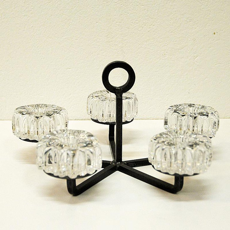 A lovely crystal glass and cast iron candleholder by Norwegian designer Willy Johansson for Hadeland Glassverk in Norway 1970s. The candleholders are made of crystal glass and named Nautilus and each have a hole for a candle light in the middle.