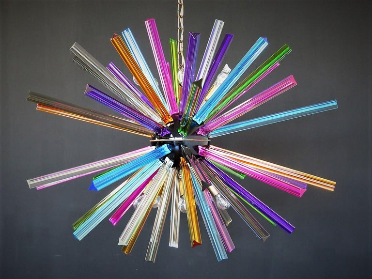 Sputnik chandelier surrounding 50 multicolored crystal glass 'triedri' prisms radiating from a center black metal nucleus. Brass lamp holder.