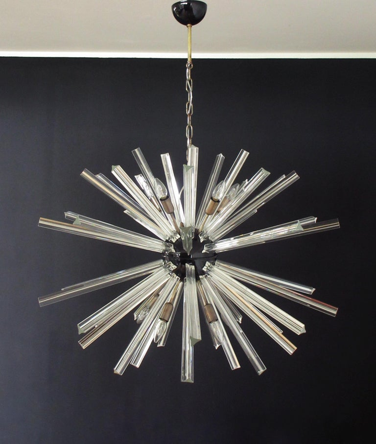 Sputnik chandelier surrounding 50 crystal glass 'triedri' prisms radiating from a center black metal nucleus. Brass lamp holder. Period: Late 20th century Dimensions: 51.20 inches (130 cm) height with chain; 27.55 inches (70 cm) height without