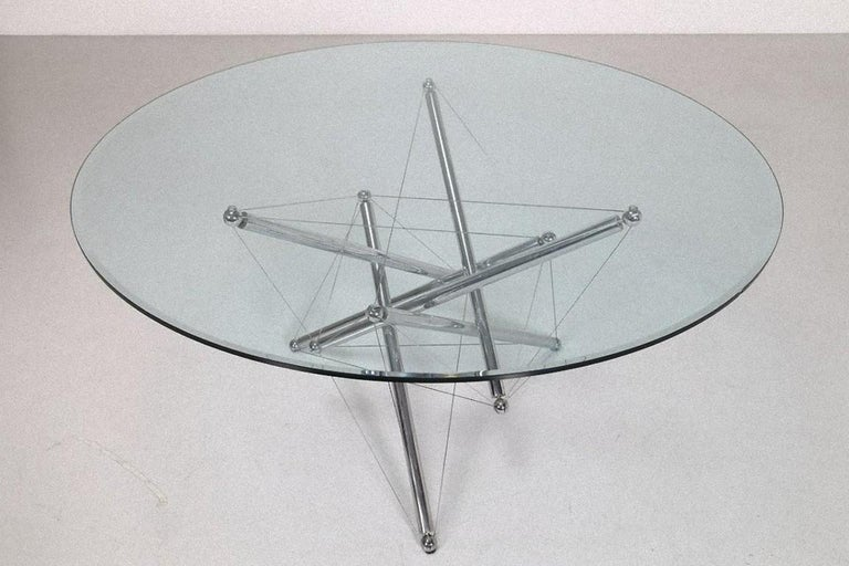 This crystal table is a design furniture designed by Theodore Waddel and produced by the Italian Company Cassina in 1973.  Table model 713 made of chromed metal and cut crystal. The table has six legs, three of which are suspended - supporting the