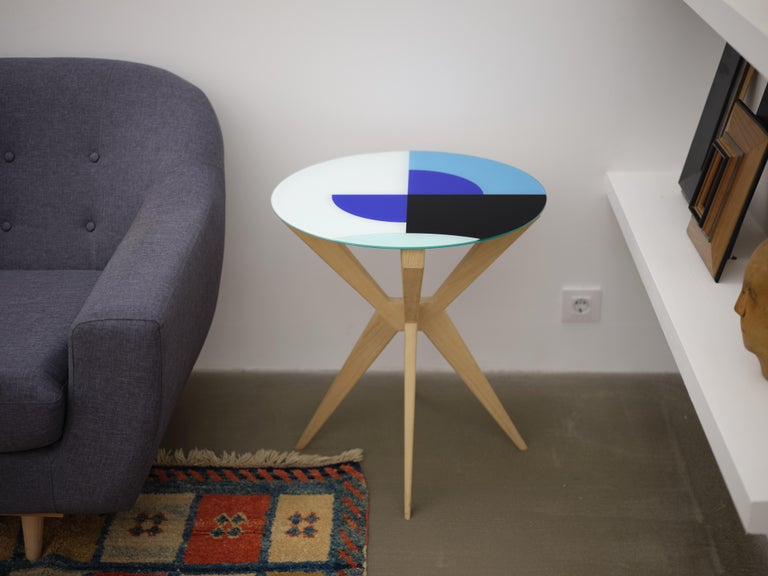Plettro is a contemporary side table. This version has a natural wood finishing and a vinyl glass top.