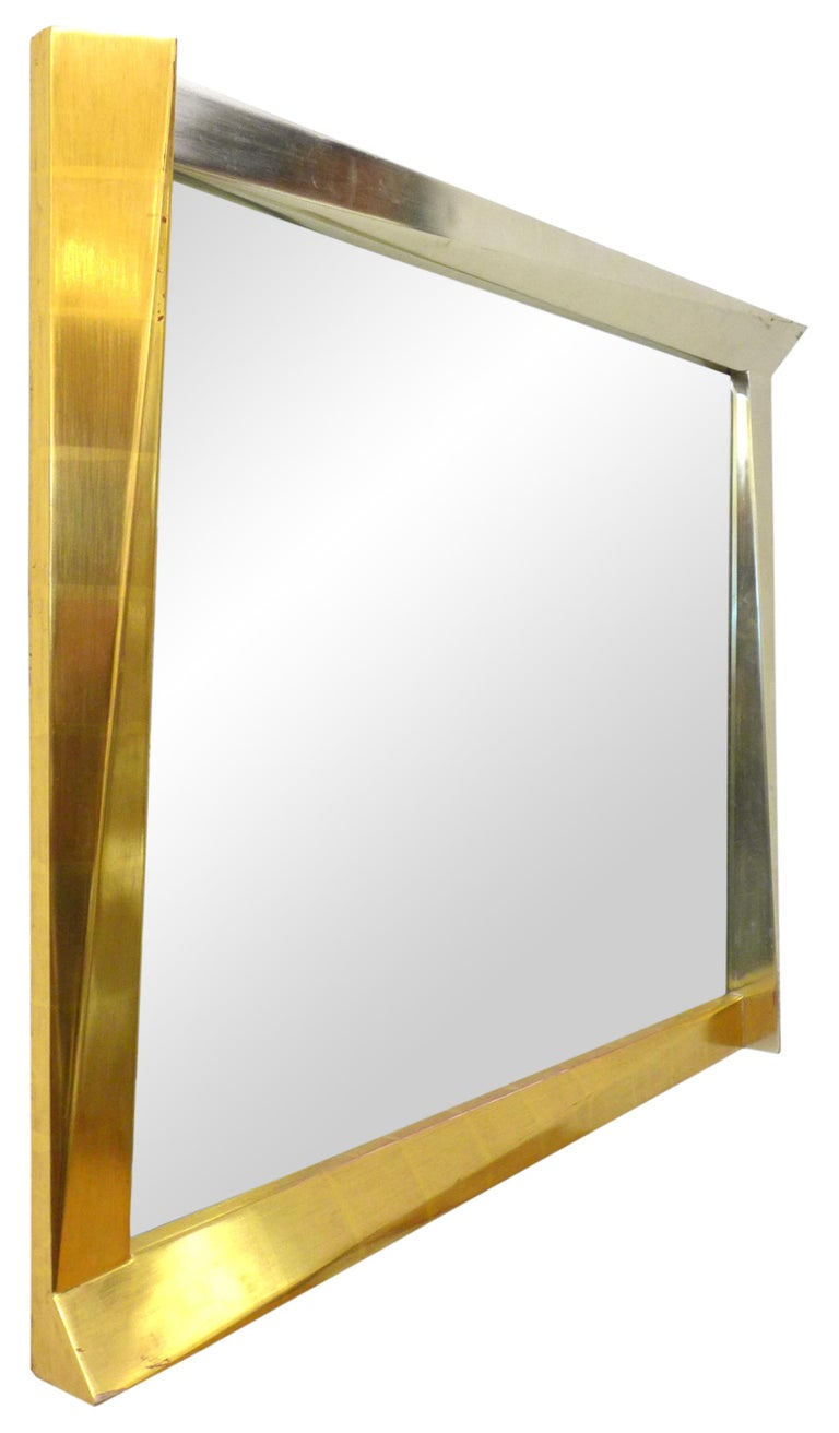 A fantastic, cubist, giltwood-framed mirror. A wonderful, optically-alluring geometric frame playfully jutting out of its expected space at various angles; adding to the illusion, a subtle gold gradient change diagonally across its entirety. Chic