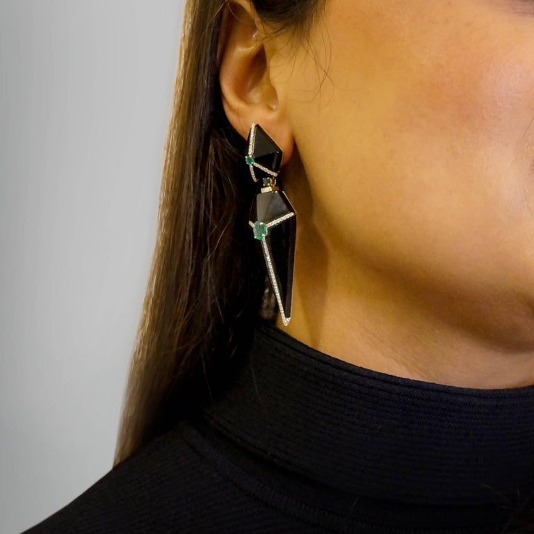 A captivating design, Ri Noor's Cubist Onyx Earrings with Emeralds and Diamonds boldly feature glossy black geometric forms created of carved onyx with 14k yellow gold accents. The fashionable earrings feature unenhanced emeralds accented by