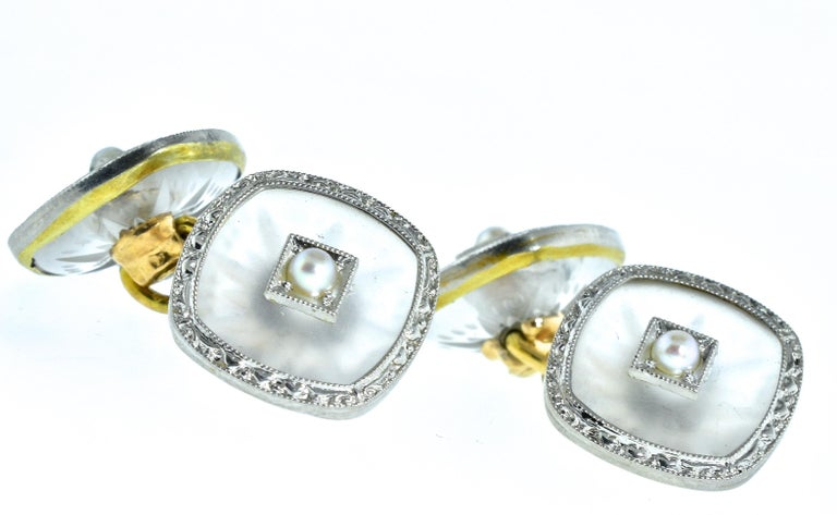 Art Deco cufflinks, circa 1930, centering a small seed pearl set in the frosted Rock Crystal and rimmed in both white and yellow gold with an etched design in the white gold.  These back to back cufflink are in fine condition.  The face of each is