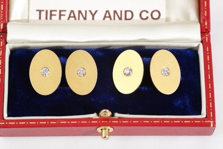 A pair of Tiffany and Co. 18 karat yellow gold double sided cufflinks of oval form, with a fine and original patina, the centre set with an old cut brilliant diamond. Signed Tiffany & Co and stamped 18k for 18 karat gold. Measures 13mm in width and