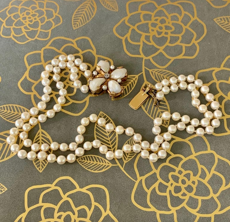 This double strand 6.5mm cream-colored cultured Pearl necklace features a custom made Pearl and Diamond clasp.  The Diamond is mine cut, 3.9mm in size and weighing approximately .25cts.  The clasp also features four Mississippi fan-shaped Pearls