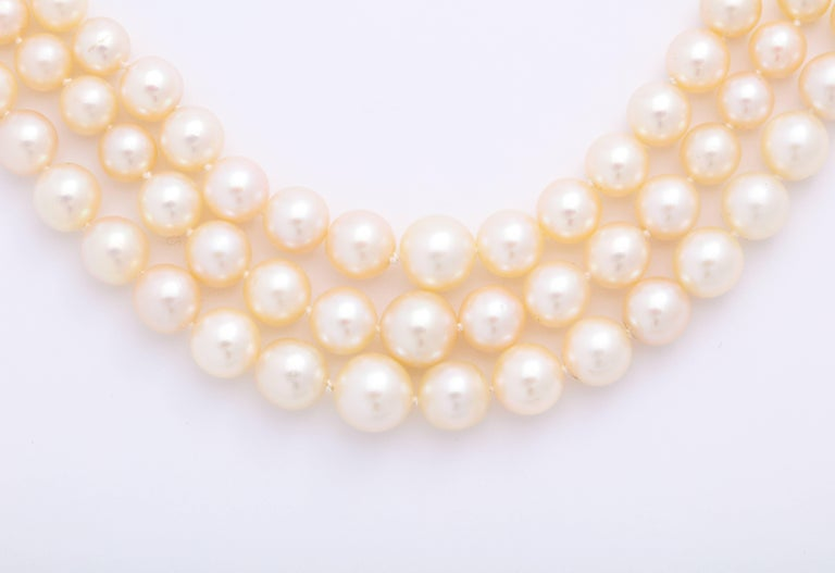 A 3-row cultured pearl necklace ranging from 4.2mm - 8.16mm. The clasp is vintage, silver-topped 18 karat yellow gold with a button pearl center surrounded by 12 old mine cut diamonds weighing an estimated 1.80 carats in total.