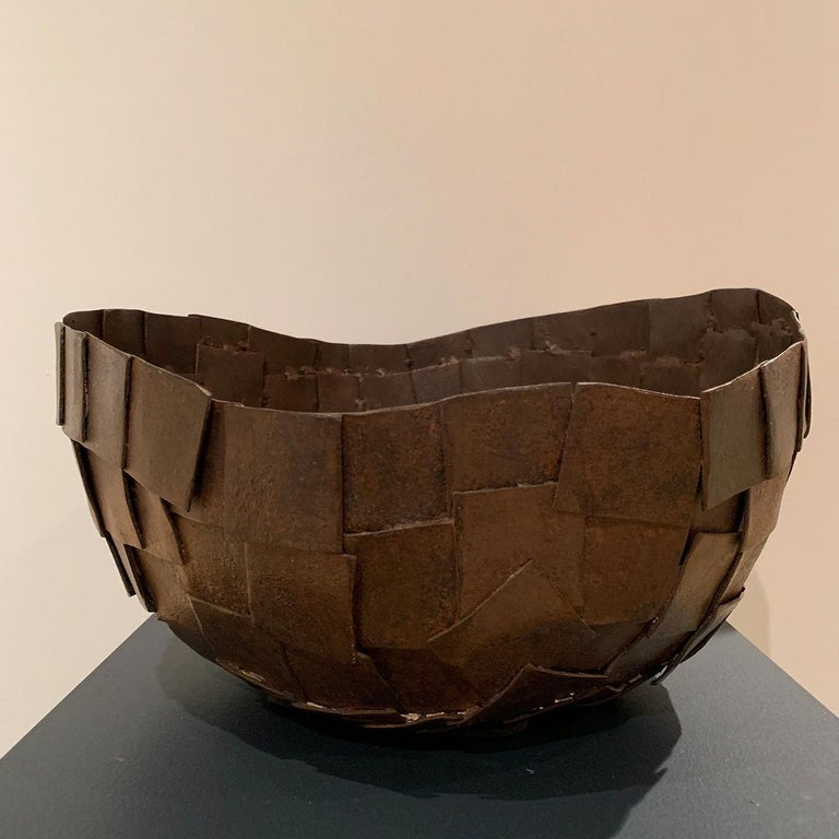 This striking vase is made with small sheets of curved metal and assembled with a dense texture; the finishing is obtained with rust and various wax passages, that obtains a patina that resembles the leather, from which the name.