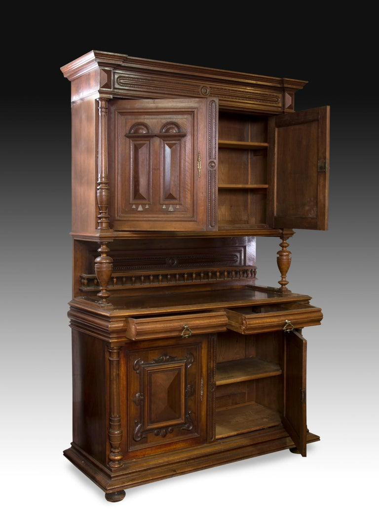 Double body cupboard with decorated front made of carved walnut wood. The lower body has a decoration on both doors, enhanced with columns on the sides; Similar composition is found in the upper body, varying the decorative theme of the doors. In