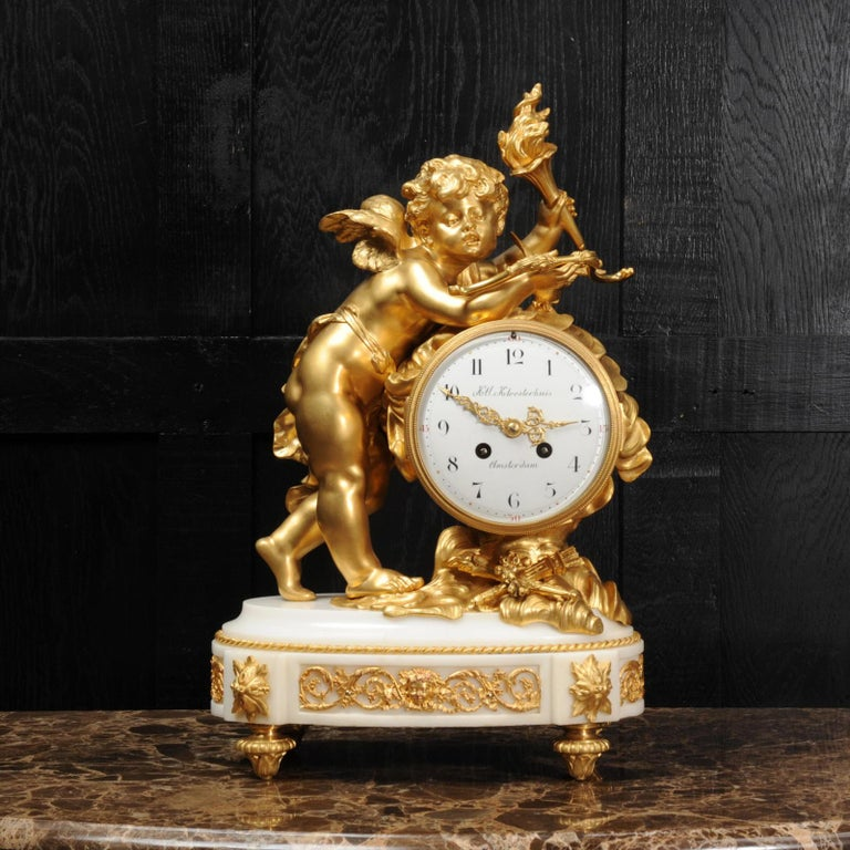 A large and stunning original antique French clock of the highest quality. It depicts Cupid among the clouds, carrying a flaming torch with which to enflame his victims with love and a bow from which he has fired an arrow. Between his arms is a