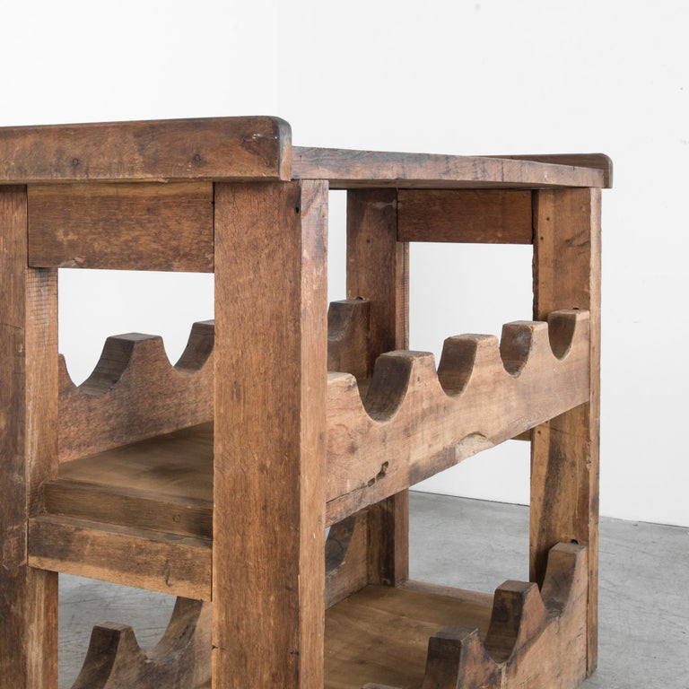From France, circa 1950, a sturdy table with two lower shelves in oak. A unique shape suggests a mysterious prior use, with a well worn patina and pattern of large circular notches. The dynamic shape makes this piece a distinctive accent in your