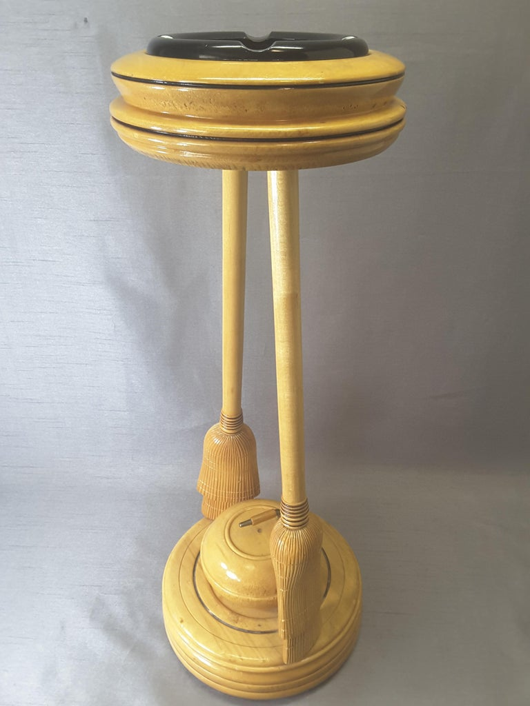 Curling Bonspiel trophy stand-up ashtray, early 1960s, The stand is maple with two curling brooms holding the top ashtray with the base mounted on a turned base and centered by a curling stone. The stand is made of maple, with a black glass ashtray.
