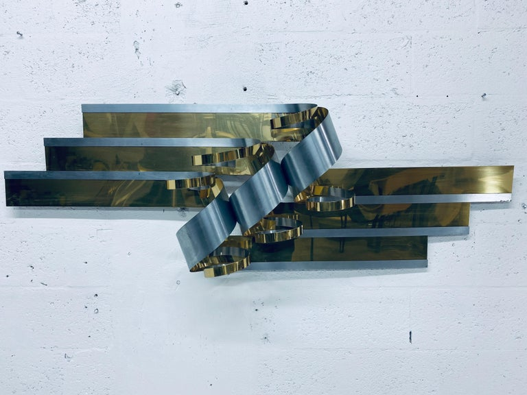 Curtis Jere ribbon wall sculpture made of brass and steel, 1989. Can be hung horizontal or vertical.
