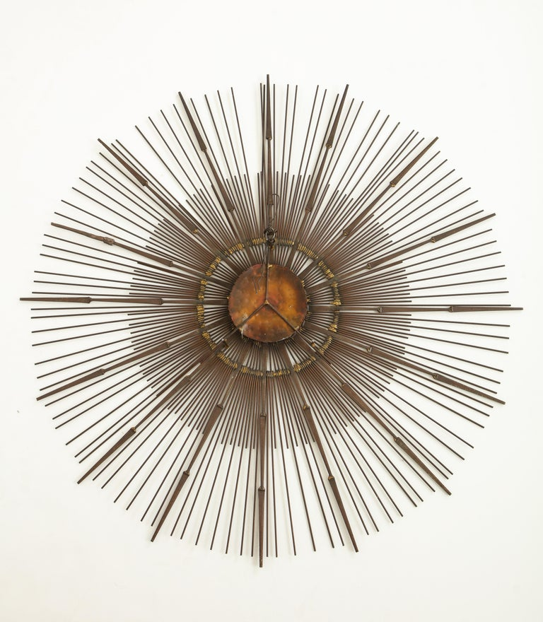 Brass wall sunburst sculpture by Curtis Jere, having one tier of rounded rods and one tier of pointed rods radiating around a central copper disc.