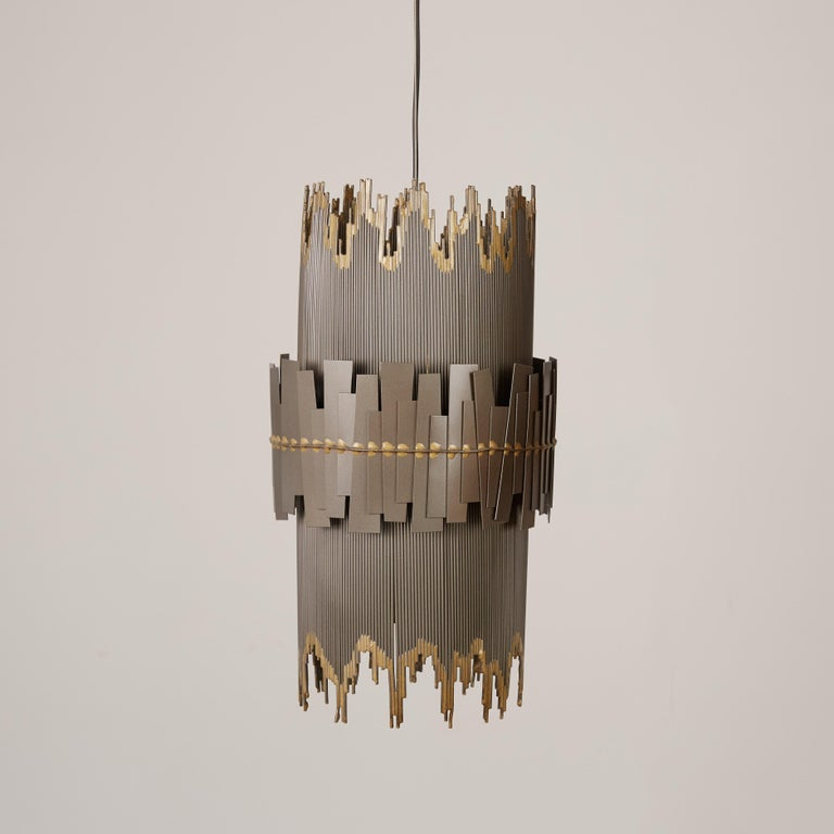 A brutalist metal pendant lamp with a cylindrical shape and irregular edges by Curtis Jeré. The main shape of the fixture has a striated frame with contrasting edges; a slightly wider ring of irregularly welded metal pieces wraps the central