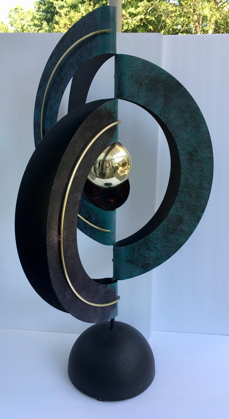 """Curtis Jere table sculpture. This sculptural piece of art is composed of three polychrome enamel decorated and folded sheet metal circles centering a split gold-tone sphere and raised on a domed metal base, signed and dated """"C Jere 1992"""",  Late"""