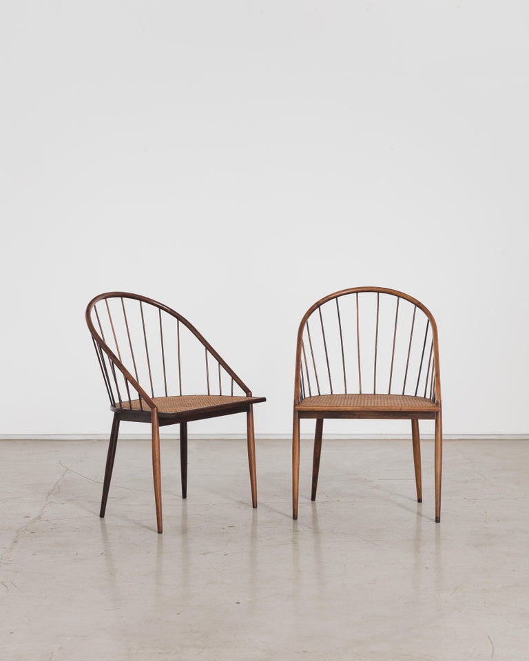 This exquisitely crafted rosewood curved chair with stick back designed by Joaquim Tenreiro (1906-1992) evokes a refined coexistence of traditional values and modern aesthetics. Its delicate shapes, with the backs of thin sticks and the carved,