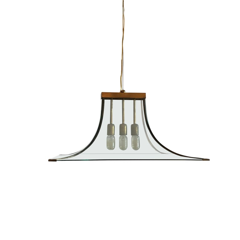 Rectangular curved clear glass chandelier with brass trim.