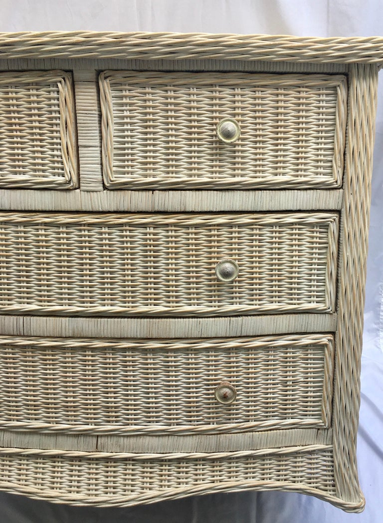 Sculptural washed wicker storage chest of drawers. This textural woven wicker cabinet features a curved serpentine draped front and four easy glide drawers. In the style of Henry Link.