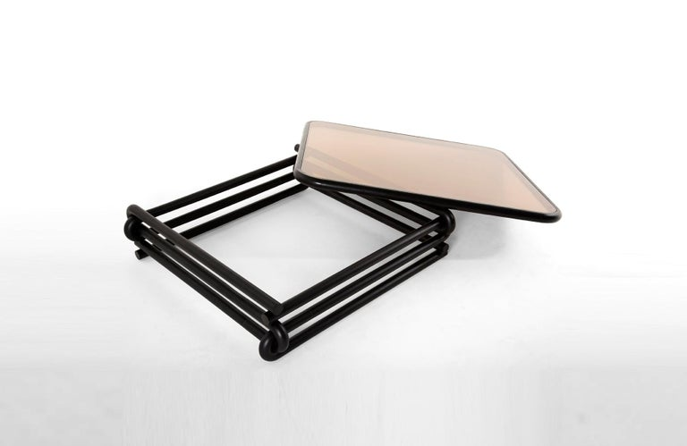 Eight U-shaped curves interlock each other to create a square base structure. A series of bevels etched into the table help to emphasize the attaching points. A double pane bronze glass top is bordered with eased hardwood edges. Café Con Leche is
