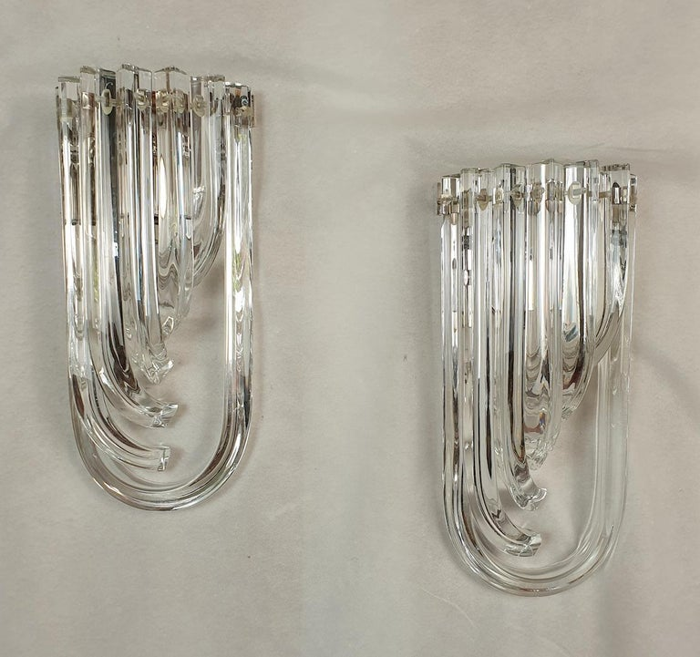 Pair of curved unusual Murano glass wall sconces, by Venini Italy, 1980s. Two pairs available; priced and sold by pair. The Mid-Century Modern pair is made of curved hand blown clear Murano glass Triedri, on a chrome frame. A timeless design,