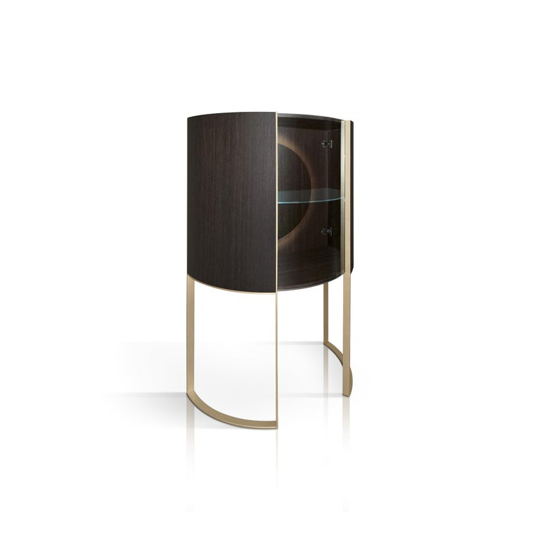 Modern functionality and harmonious aesthetics merge in this stunning display cabinet that brings to life the Classic concept of the showcase in a unique, modern design. The open base, with two brass U-shaped legs that follow the round profile of