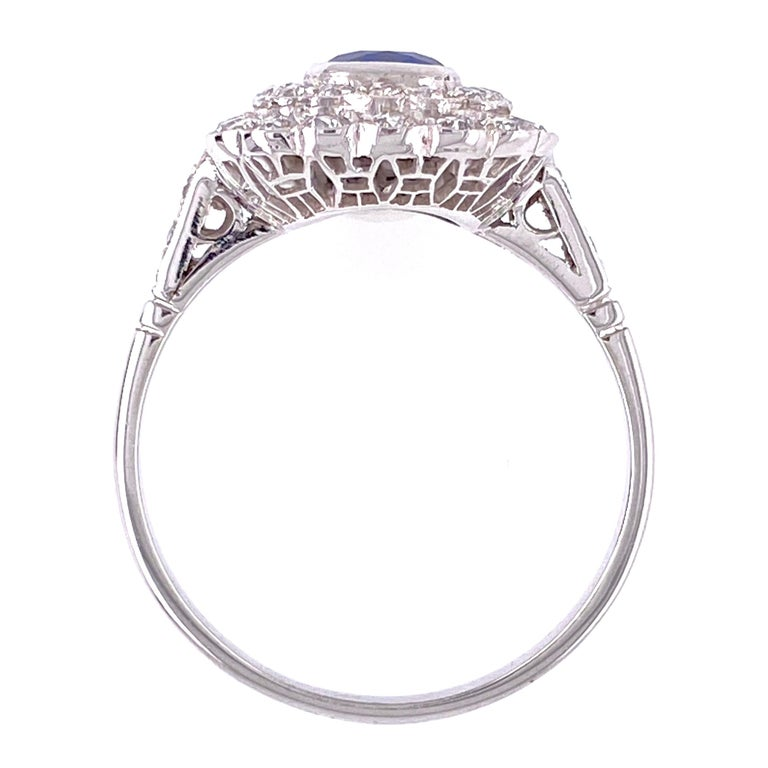 Classic and finely detailed Sapphire Cocktail Ring, center securely set with a 0.75 Carat Cushion Blue Sapphire surrounded by Diamonds, weighing approx. 0.80 total carat weight. Beautifully Hand crafted Platinum mounting. Ring size 7.75, resizing
