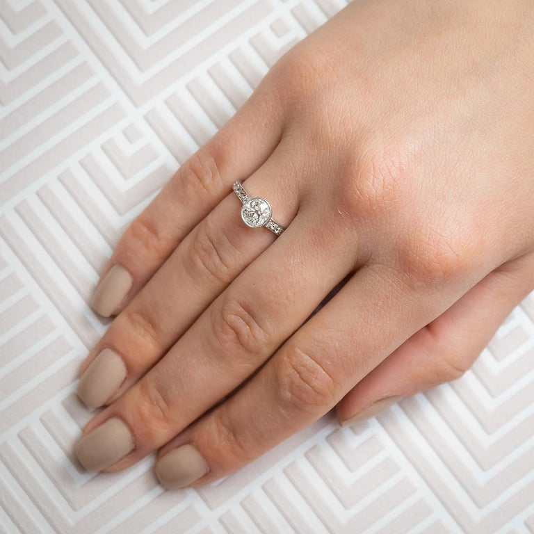 An Edwardian style single stone diamond ring, set with an estimated 1.20ct old cushion-cut diamond, in a millegrain setting with round brilliant-cut diamond, pavé set shoulders, mounted in platinum. Stamped with a French dog's head mark to the
