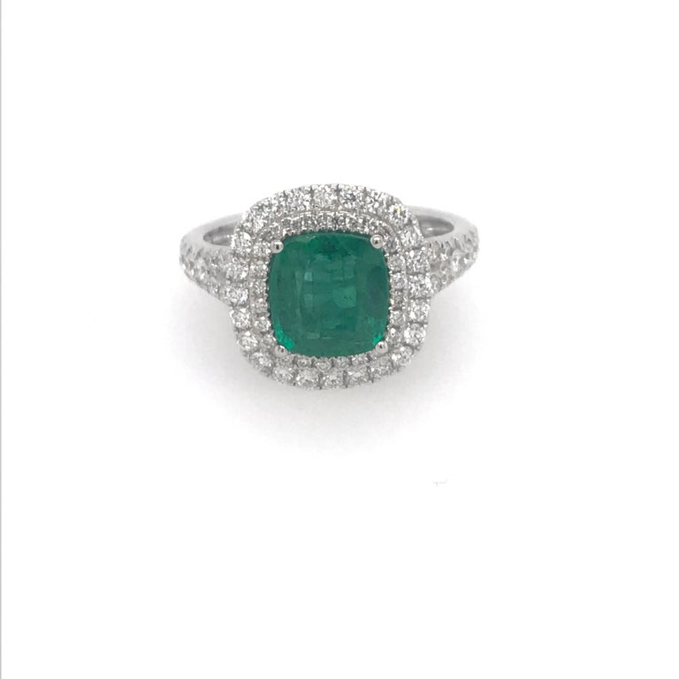 18K White gold ring featuring one cushion cut green emerald weighing 1.99 carats flanked with a double halo and split shank weighing 0.65 carats. Color G-H Clarity SI  A beautiful ring!!!